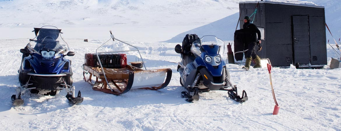 snowmobiles-setting-on-rib-lake-in-front-of-ice-fishing-shack
